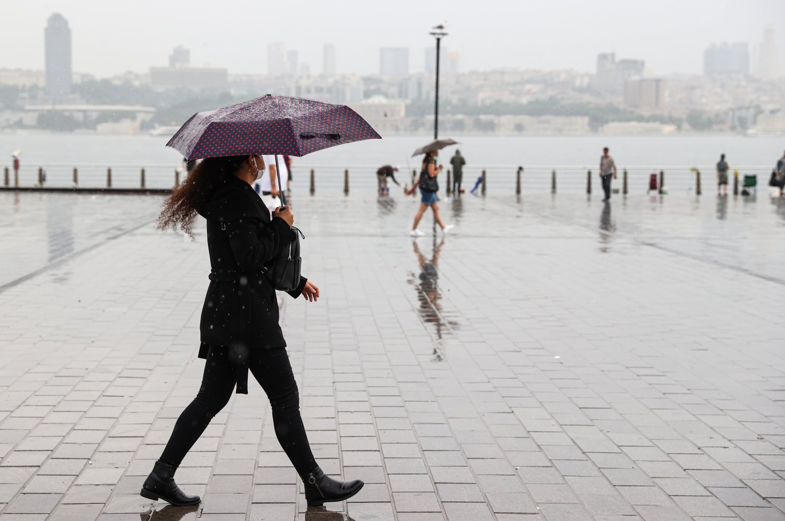 A woman walks in the rain, in Istanbul, Turkey, July 6, 2021. (AA PHOTO)