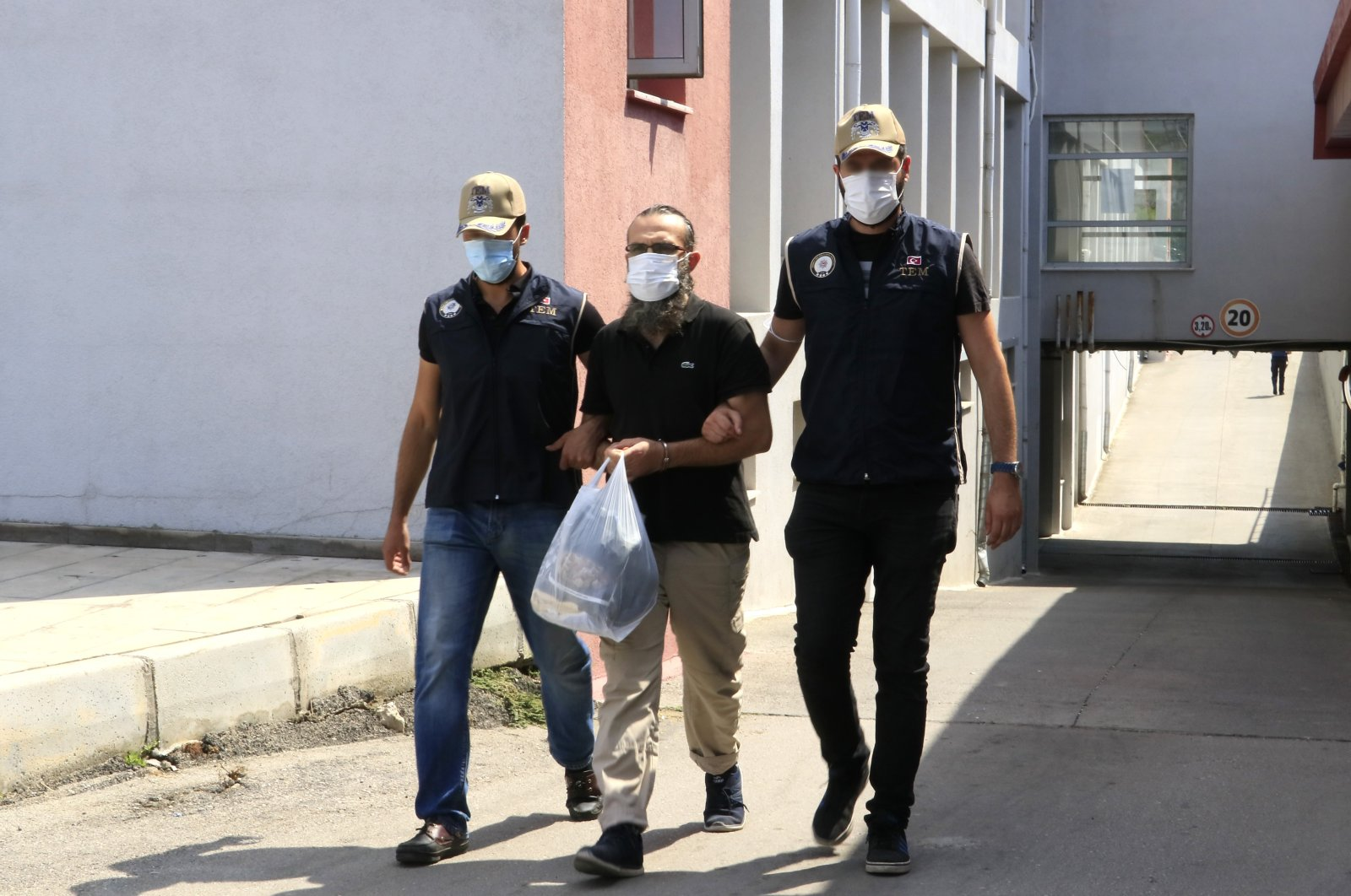 Police officers escort Daesh terrorist Irfan Ç. (C) in Adana province, July 6, 2021. (IHA Photo)