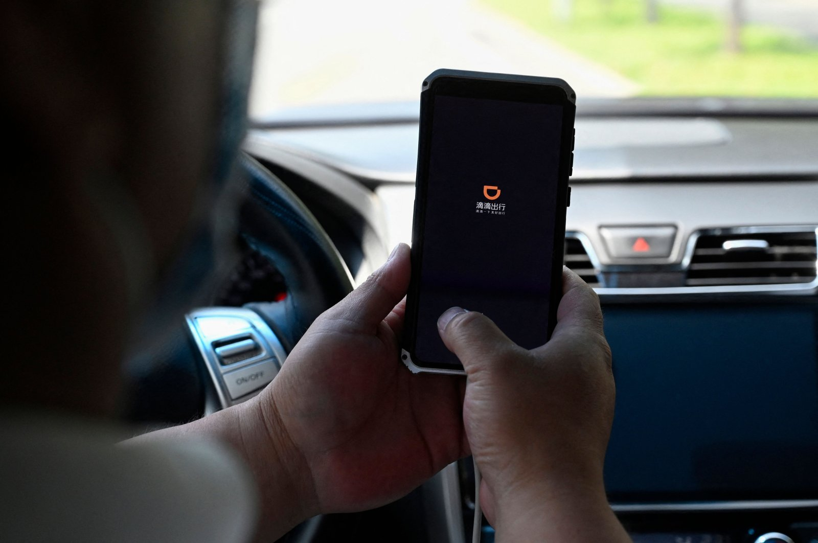 A driver opening the Didi Chuxing ride-hailing app on his smartphone in Beijing, China, July 2, 2021. (AFP Photo)