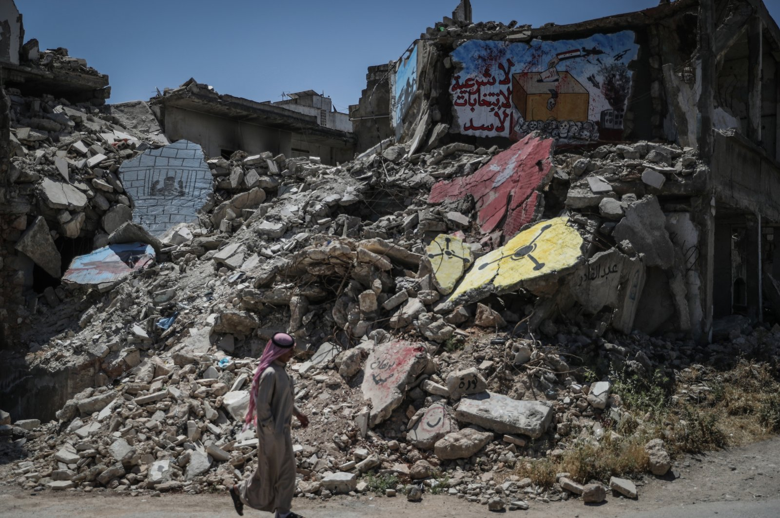 """Graffiti in Arabic that reads """"No legitimacy of Assad's elections""""is seen painted on the remains of a destroyed building, Idlib, Syria, May 26, 2021. (Getty Images)"""