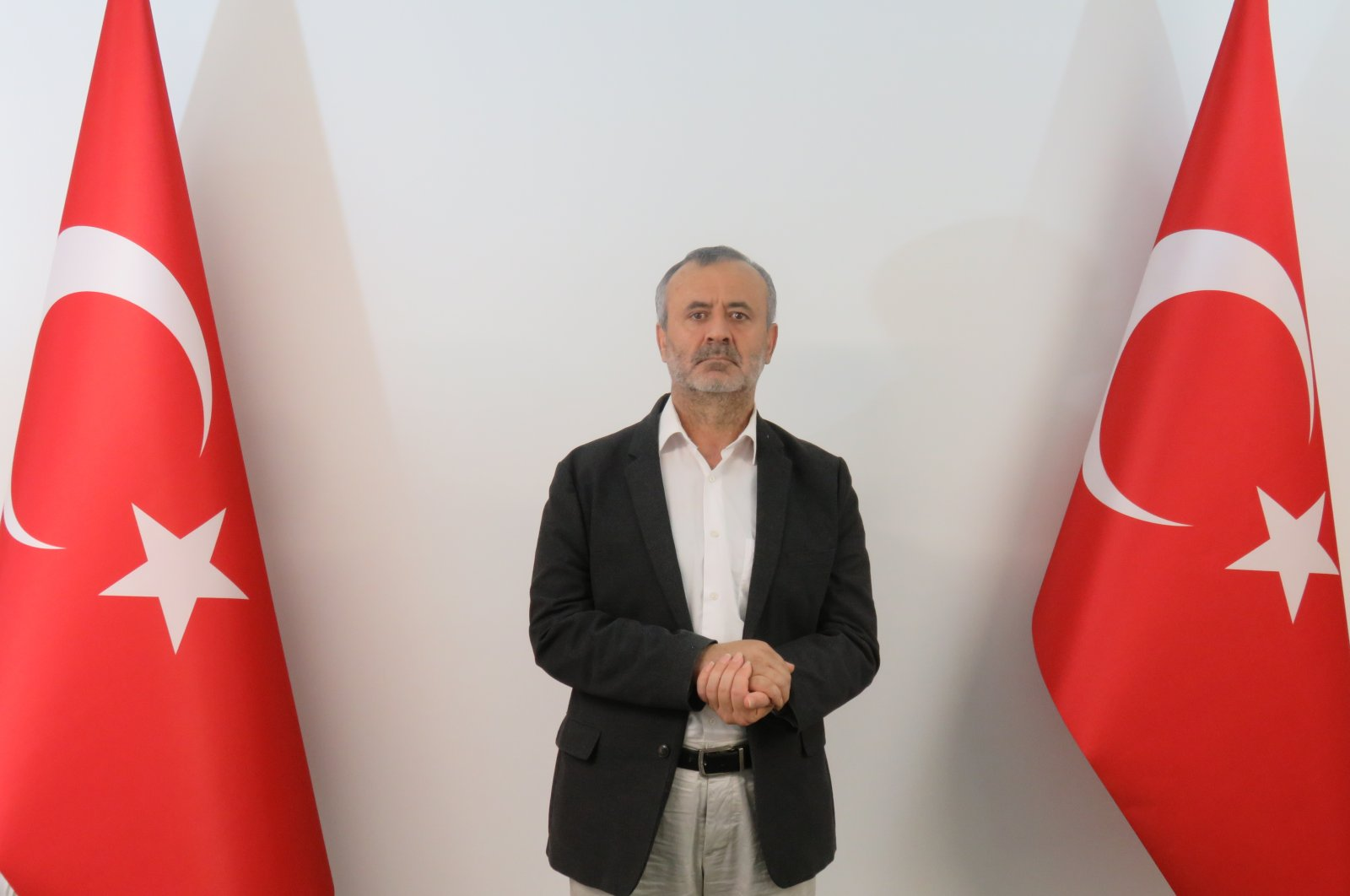 Orhan Inandı poses between two Turkish flags in this photo handed out to the media after he was brought to Turkey, July 5, 2021. (AA PHOTO)