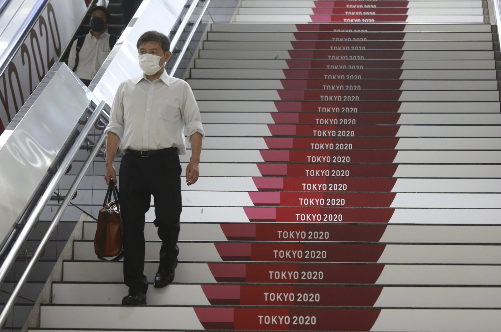 A man wearing a face mask goes down a flight of stairs showing Tokyo 2020 banners, Tokyo, July 6, 2021. (AP Photo)