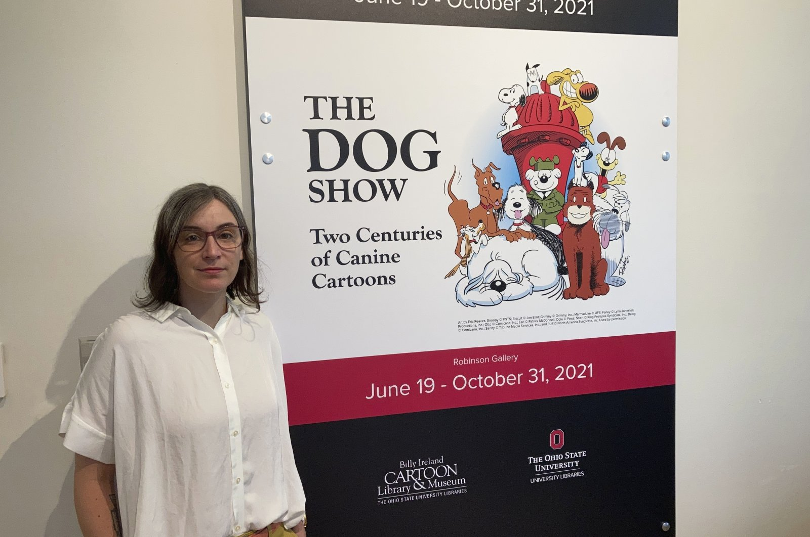 """Anne Drozd, museum coordinator at The Ohio State University's Billy Ireland Cartoon Library Museum, stands at the entrance to the library's new exhibit, """"The Dog Show,""""Columbus, Ohio, U.S., June 24, 2021. (AP Photo)"""