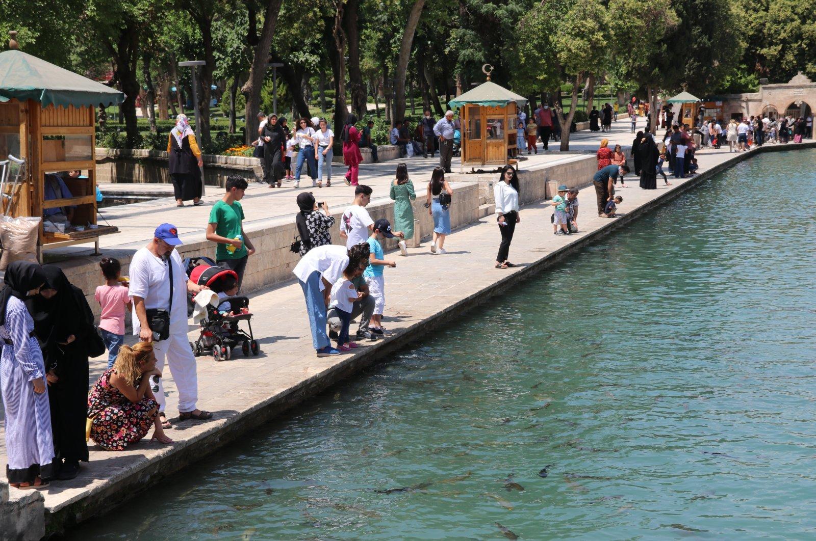 People walk on the shore of Balıklıgöl pond in Şanlıurfa, southeastern Turkey, July 2, 2021. Şanlıurfa has the highest total fertility rate in the country. (AA PHOTO)
