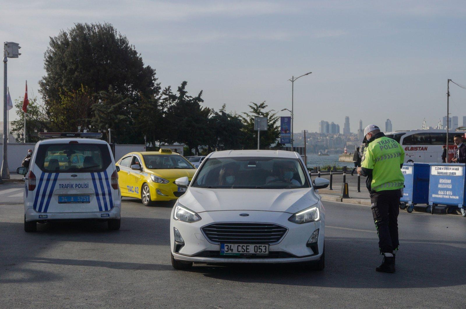 A traffic police checks a car in Üsküdar, Istanbul, Turkey, April 29, 2021.
