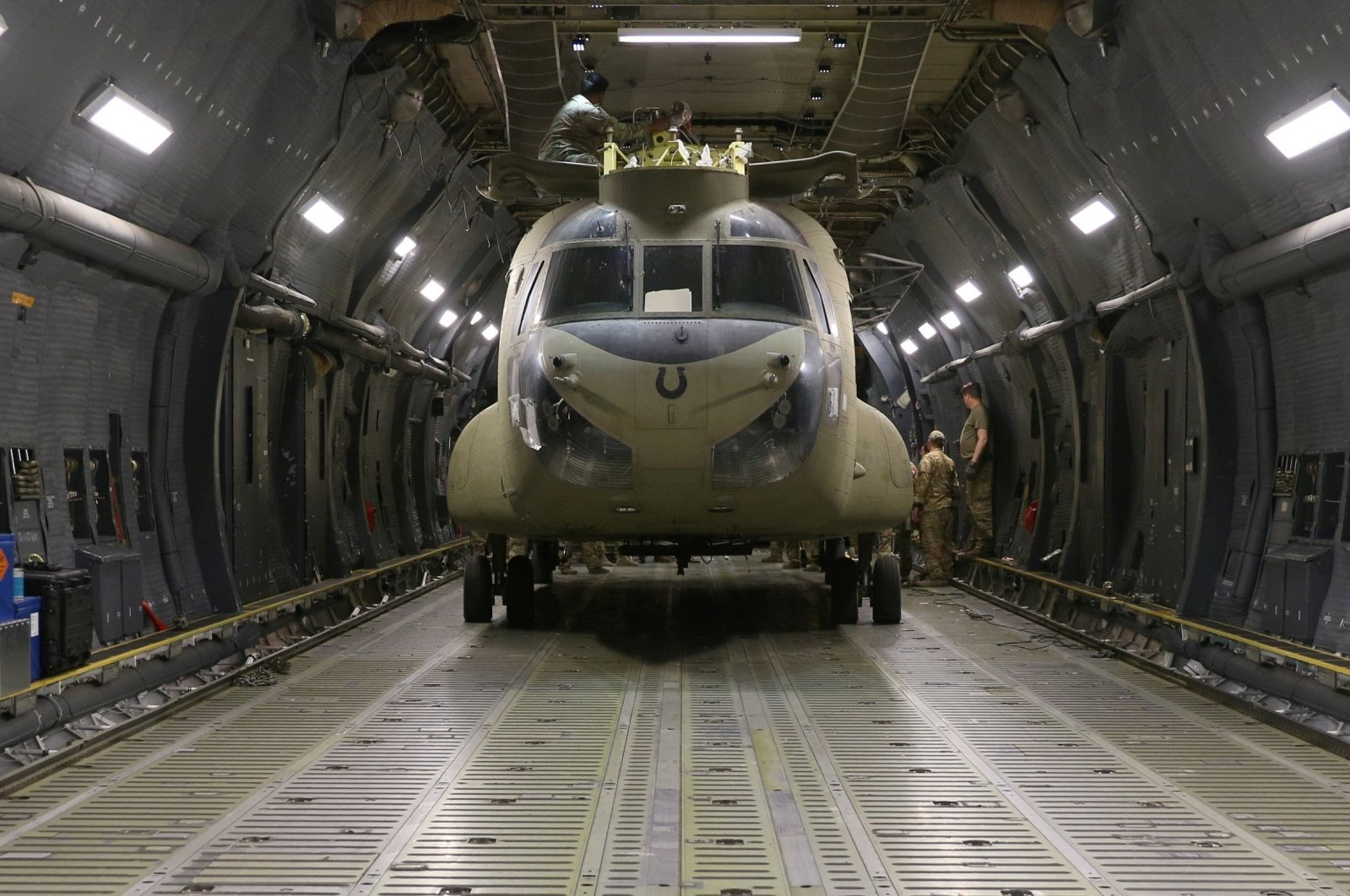 Aerial porters work with maintainers to load a CH-47 Chinook helicopter into a U.S. Air Force C-17 Globemaster III during the withdrawl of American forces from Afghanistan, June 16, 2021. (U.S. Army/Sgt. 1st Class Corey Vandiver via Reuters)