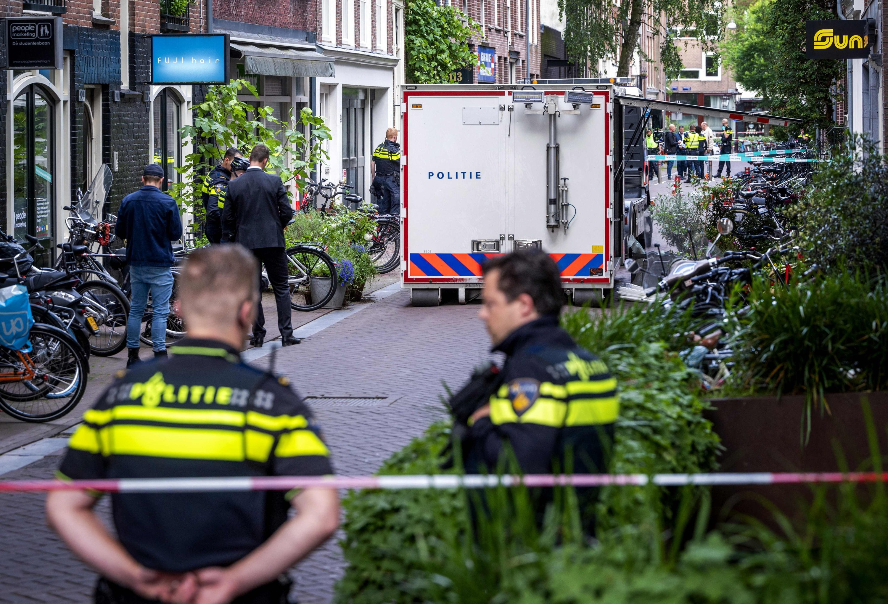 Police officers work at the site of an attack, during which a Dutch journalist specialized in crime, Peter R. de Vries, was seriously injured in a shooting in Amsterdam, the Netherlands, July 6, 2021. (AFP Photo)