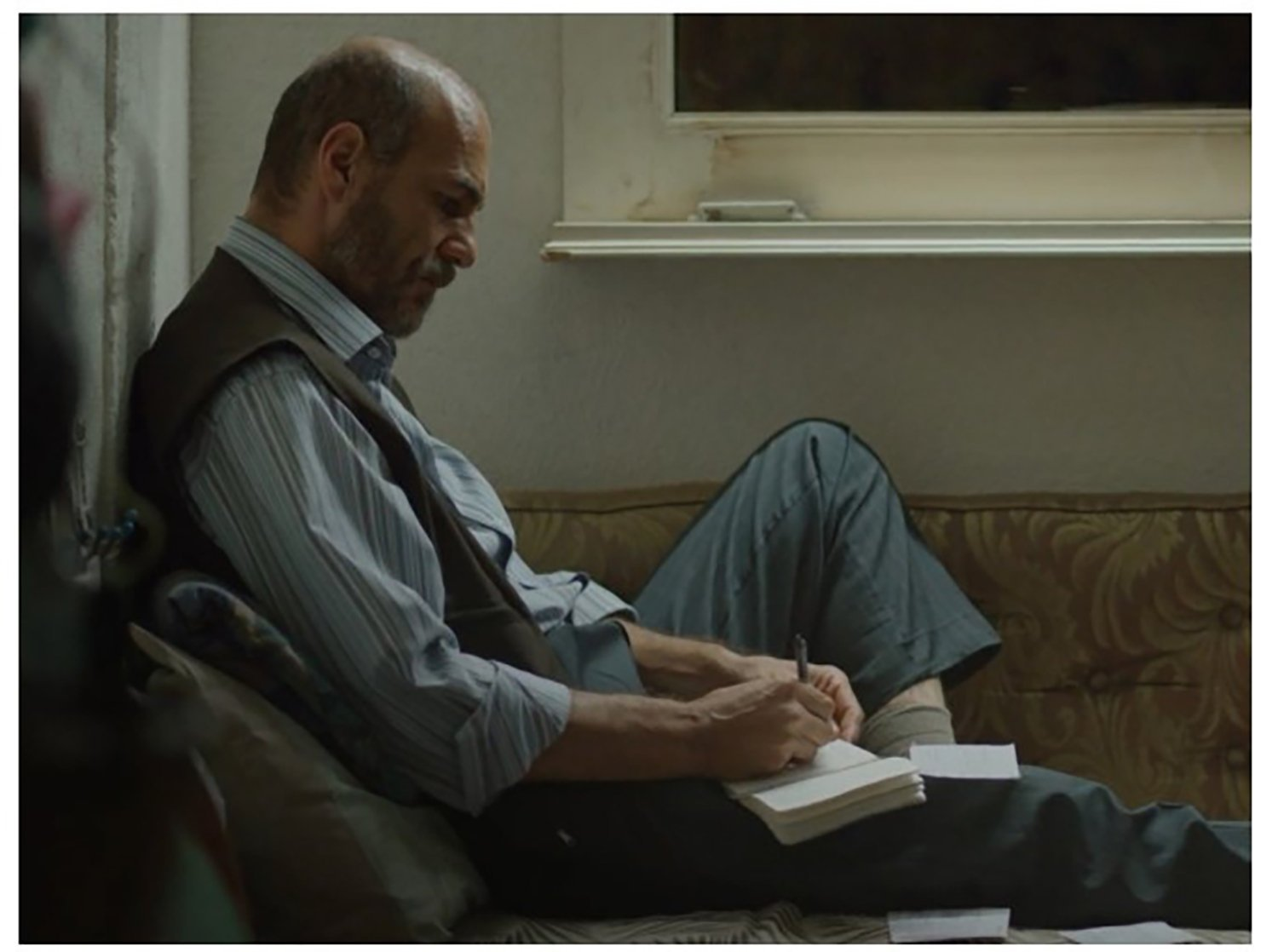"""Umut Karadağ takes notes while sitting down, in a scene from the film """"Bağlılık Hasan"""" (""""Commitment Hasan""""). (Archive Photo)"""