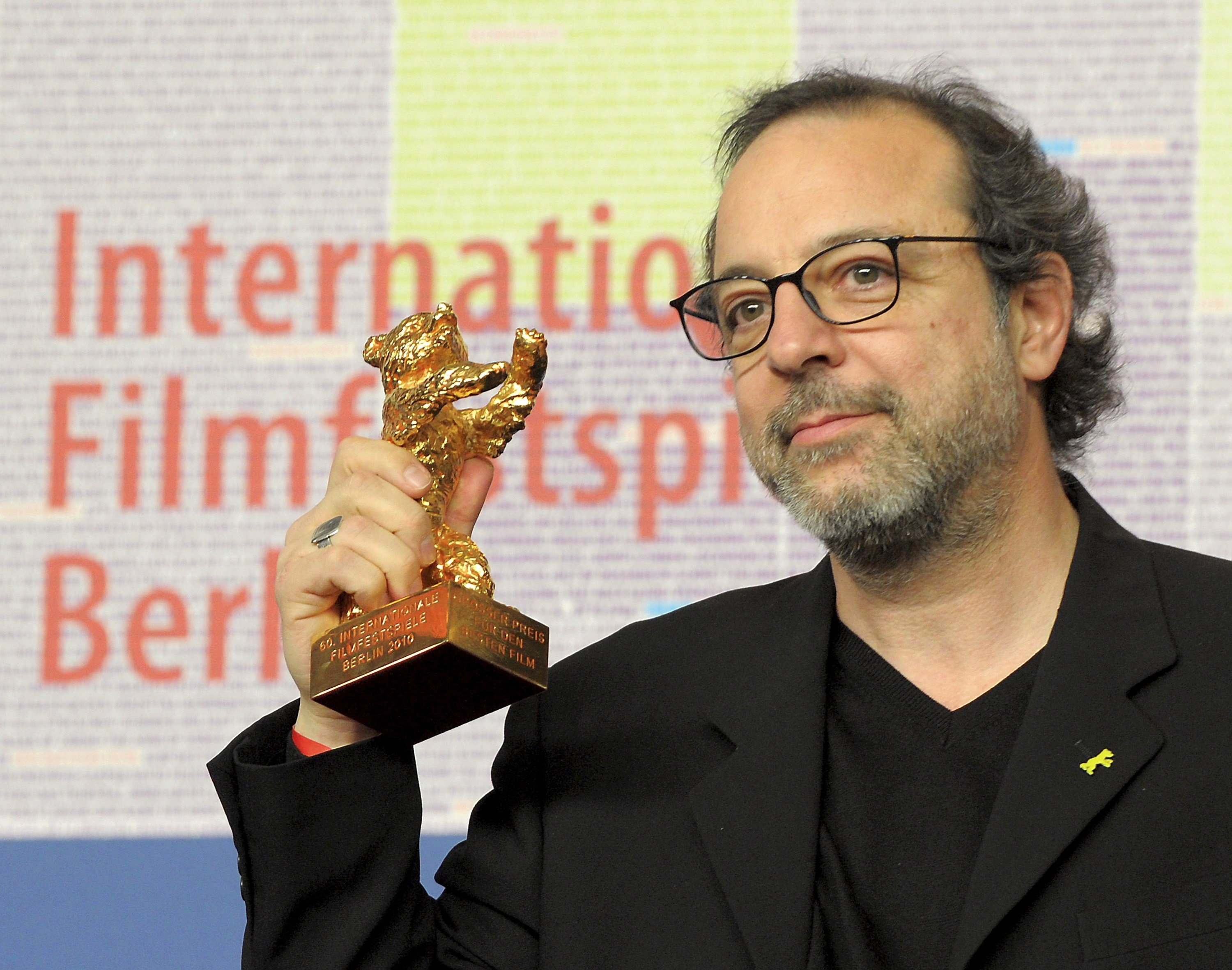 """Director Hasan Semih Kaplanoglu poses with the Golden Bear for the Best Film for the movie """"Bal"""" (Honey) during a press conference after the 60th Berlinale International Film Festival in Berlin, Germany, Feb. 20, 2010. (EPA Photo)"""