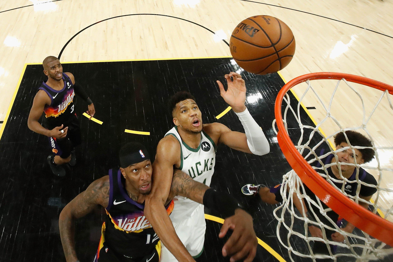 Milwaukee Bucks forward Giannis Antetokounmpo (C) shoots over Phoenix Suns forward Torrey Craig (L) during NBA Finals Game 1, Phoenix, Arizona, U.S., July 6, 2021. (Reuters Photo)