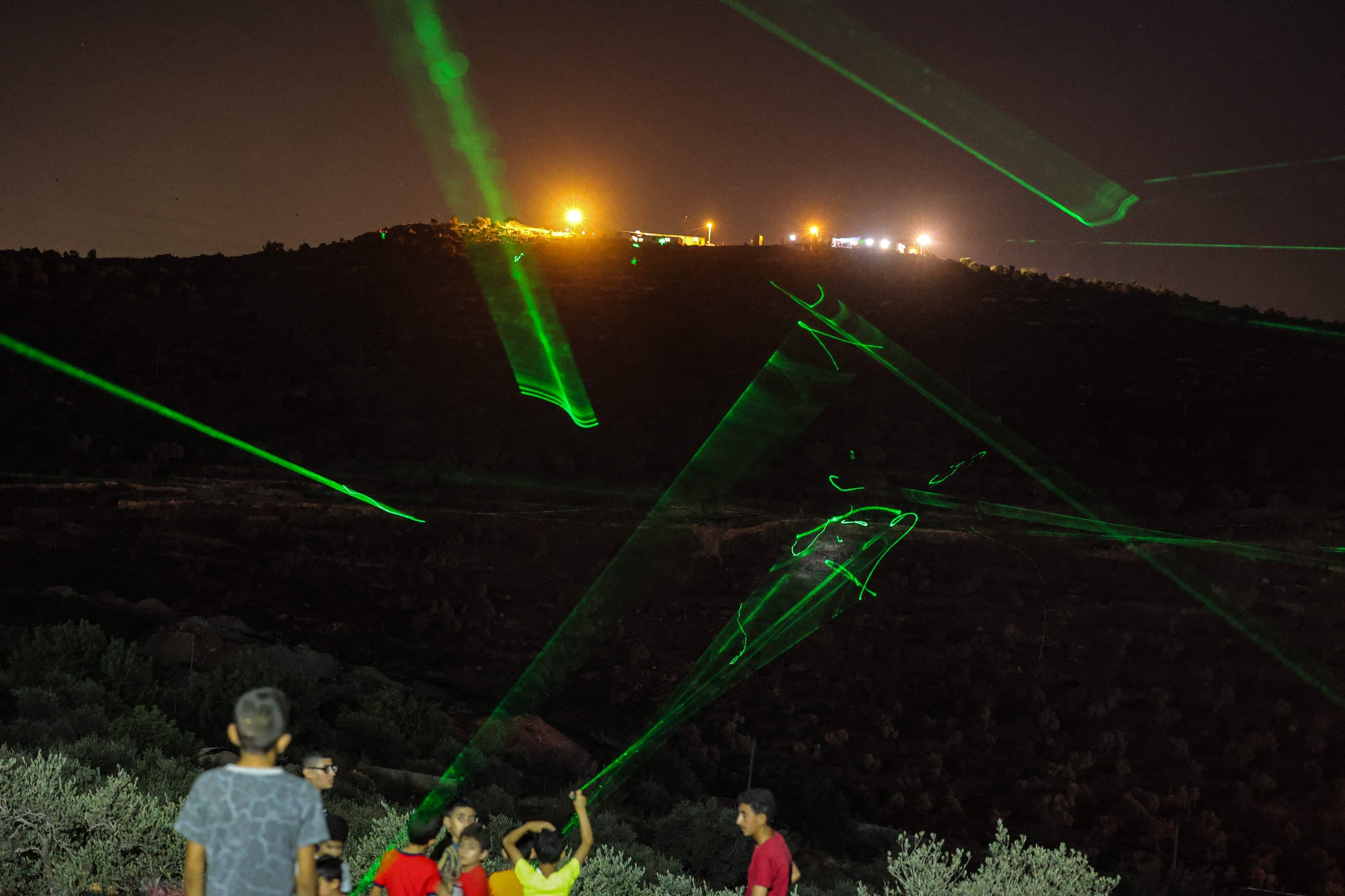 Palestinian protesters use high-powered lasers against the Israeli illegal settlers' outpost of Eviatar, the West Bank, occupied Palestine, July 1, 2021. (AFP Photo)