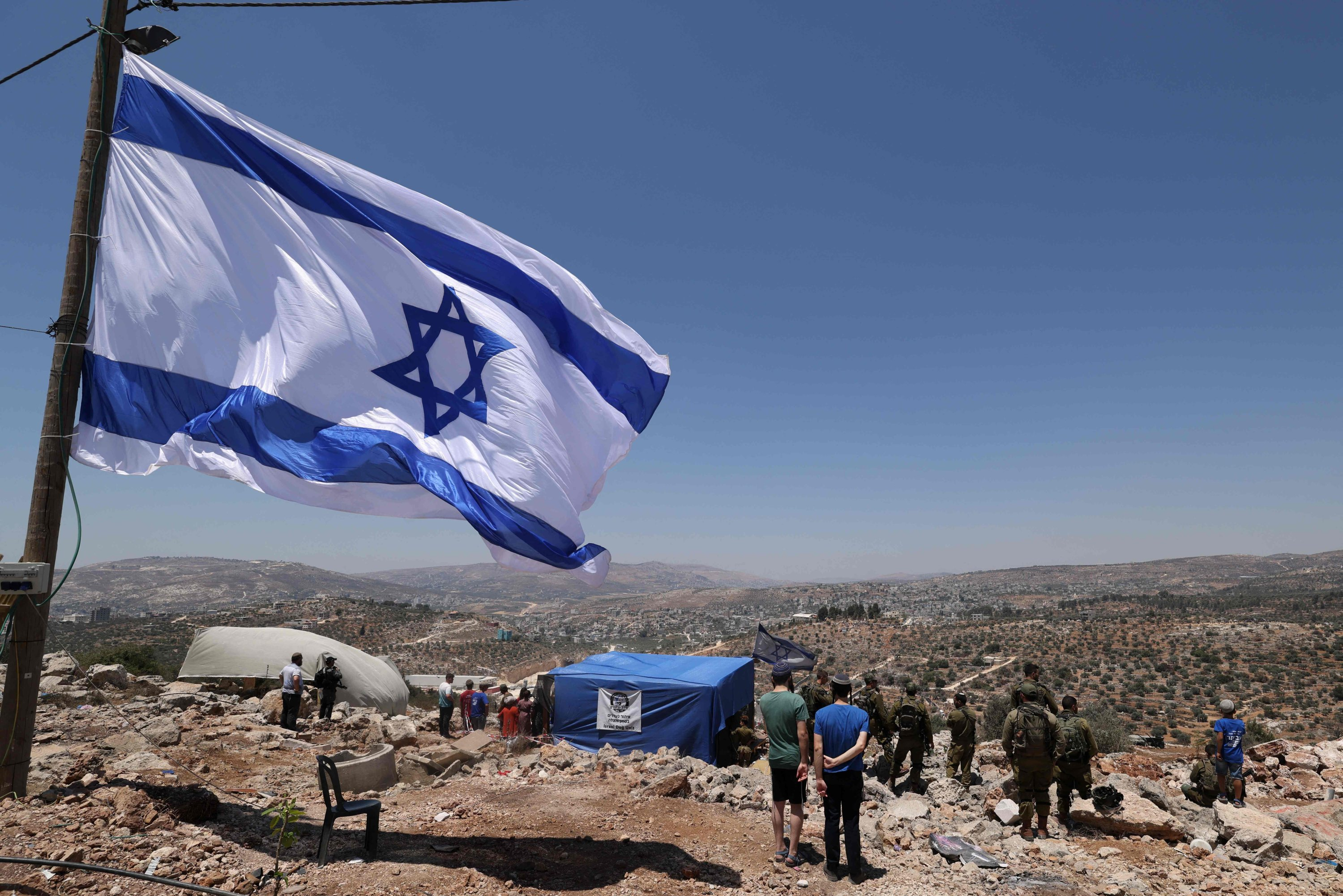 Israeli soldiers and settlers stare at the Palestinian village of Beita before evacuating the newly established wildcat outpost of Eviatar in Beita, near the northern Palestinian city of Nablus in the occupied West Bank, Palestine, July 2, 2021. (AFP Photo)
