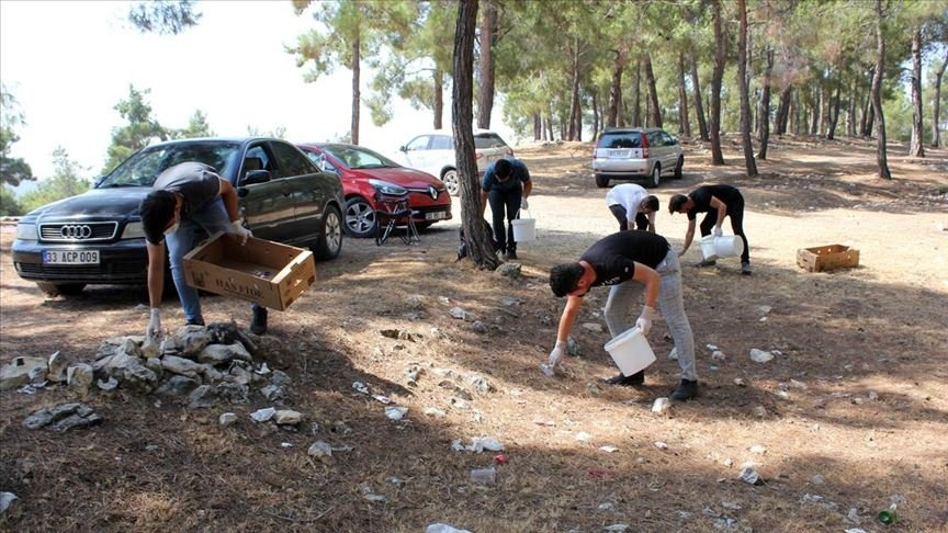 Youth collect garbage left behind by picnickers in Mersin, southern Turkey, July 29, 2020. (AA PHOTO)