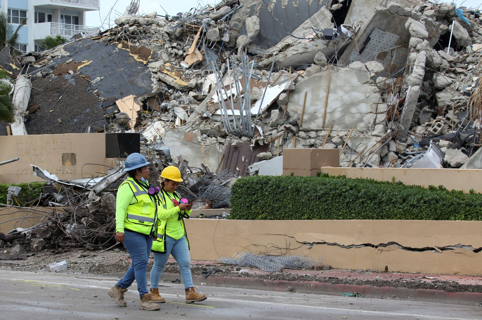 Rescue workers walk past debris after the managed demolition of the remaining part of Champlain Towers South complex as search-and-rescue efforts continue in Surfside, U.S. July 6, 2021. (Reuters Photo)