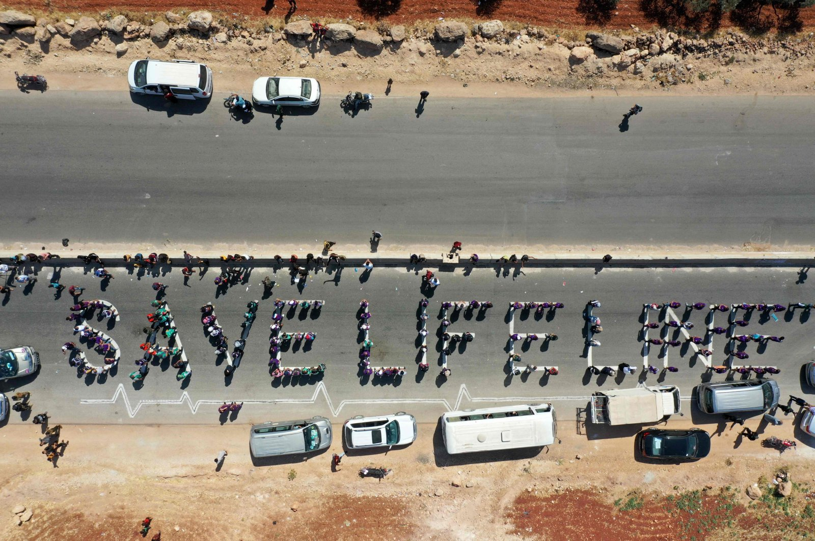 A human chain is formed by workers from the civil society, humanitarian aid and medical and rescue services in a vigil calling for maintaining a U.N. resolution authorizing the passage of humanitarian aid into Syria's opposition-held northwestern province of Idlib, July 2, 2021 (AFP Photo)