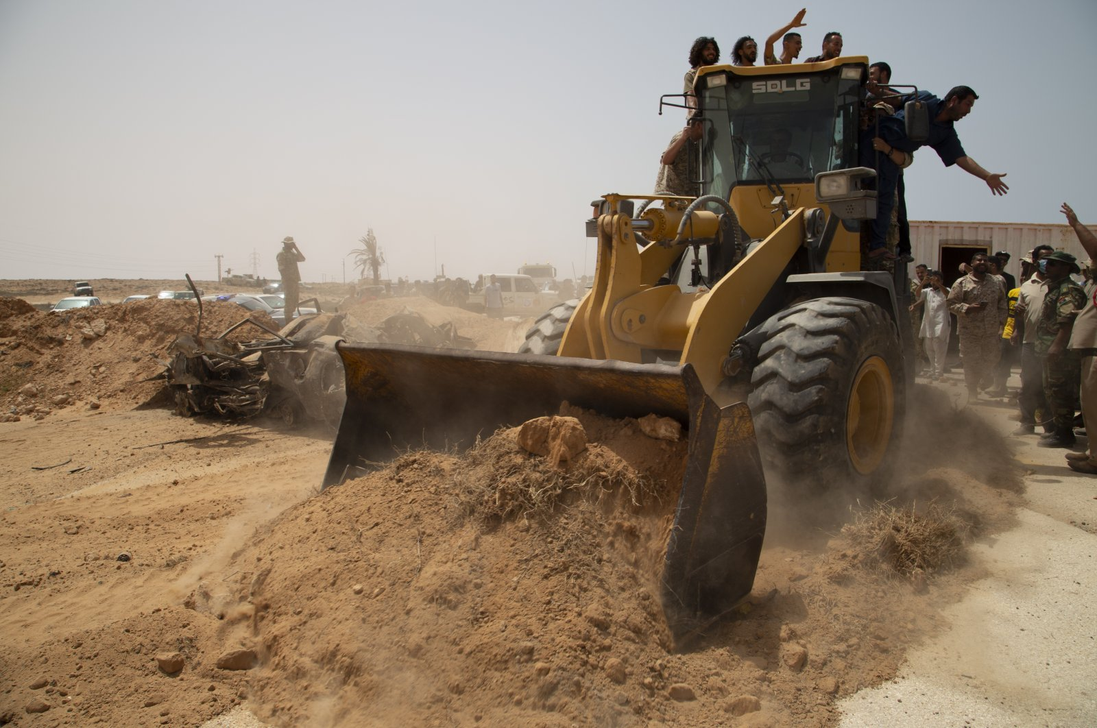 A bulldozer pushes earth during a ceremony to reopen the road between the cities of Misrata and Sirte Sunday, June 20, 2021. (AP Photo)