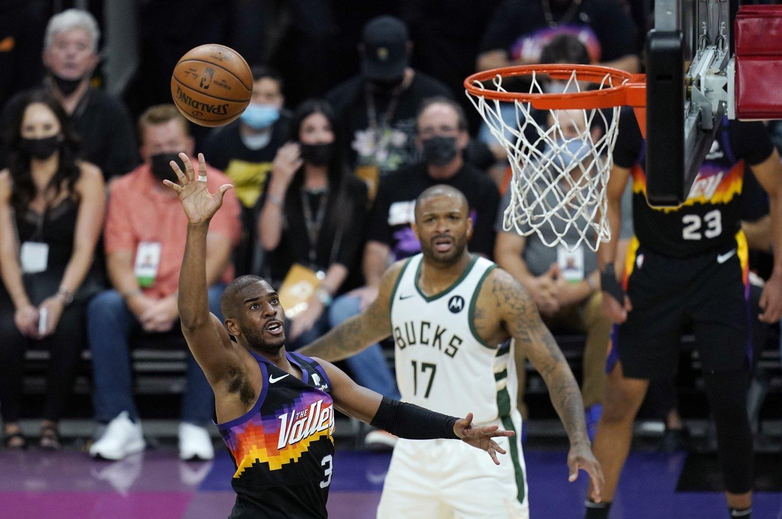 Phoenix Suns guard Chris Paul (L) scores as Milwaukee Bucks forward P.J. Tucker (R) looks on during NBA Finals Game 1, Phoenix, Arizona, U.S., July 6, 2021. (AP Photo)