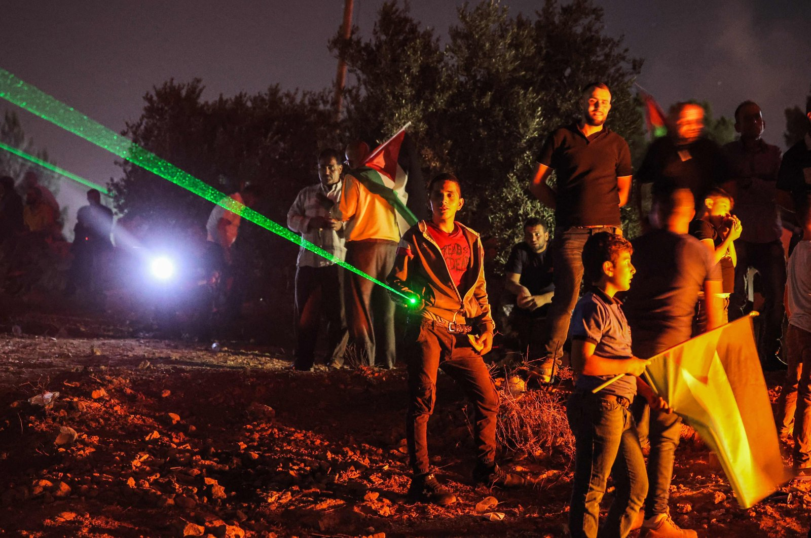 Palestinian protesters use high-powered lasers during a demonstration against the Israeli illegal settlers' outpost of Eviatar, in the town of Beita, near the occupied West Bank city of Nablus, occupied Palestine, July 1, 2021. (AFP Photo)