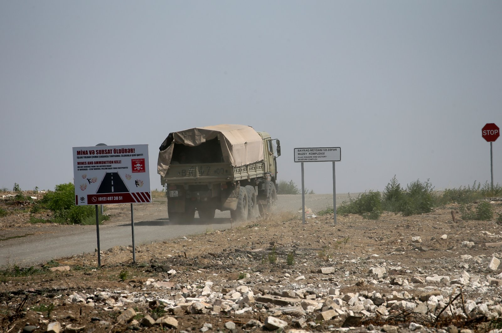 A truck moves past a sign warning of mines in the town of Agdam, Azerbaijan, July 5, 2021. (Getty Images)