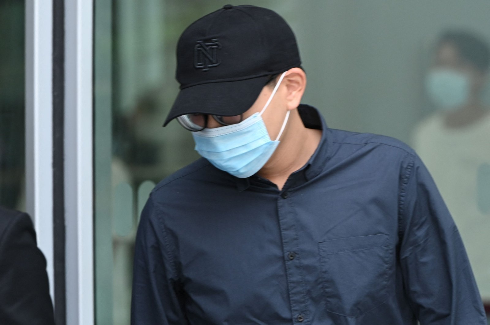 Derek Ng De Ren leaves the state court in Singapore after being sentenced to nine months probation and 40 hours of community service for sending death threats to English Premier League footballer Neal Maupay and his family, July 7, 2021. (AFP Photo)