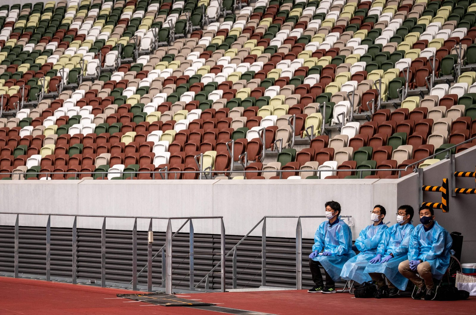 Staff members in protective clothing and masks sit next to empty seats during a para-athletics test event for the 2020 Tokyo Olympics at the National Stadium in Tokyo, Japan, May 11, 2021. (AFP Photo)