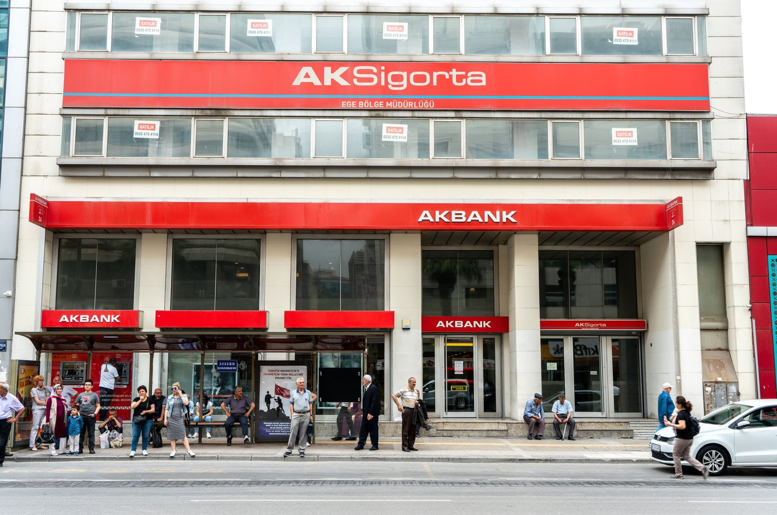 People wait at a bus stop in front of an Akbank branch in Istanbul, Turkey, May 19, 2019. (Shutterstock Photo)