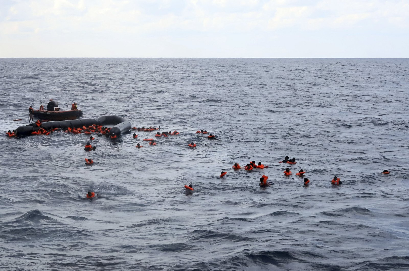 Refugees and migrants are rescued by members of the Spanish NGO Proactiva Open Arms, after leaving Libya trying to reach European soil aboard an overcrowded rubber boat in the Mediterranean sea, Nov. 11, 2020. (AP Photo)