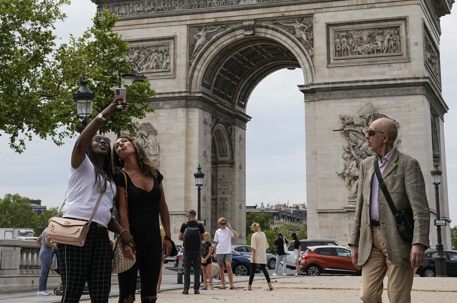 People take a selfie with the Arc de Triomphe in the background at the Champs Elysees avenue in Paris, France, June 17, 2021. (AP Photo)