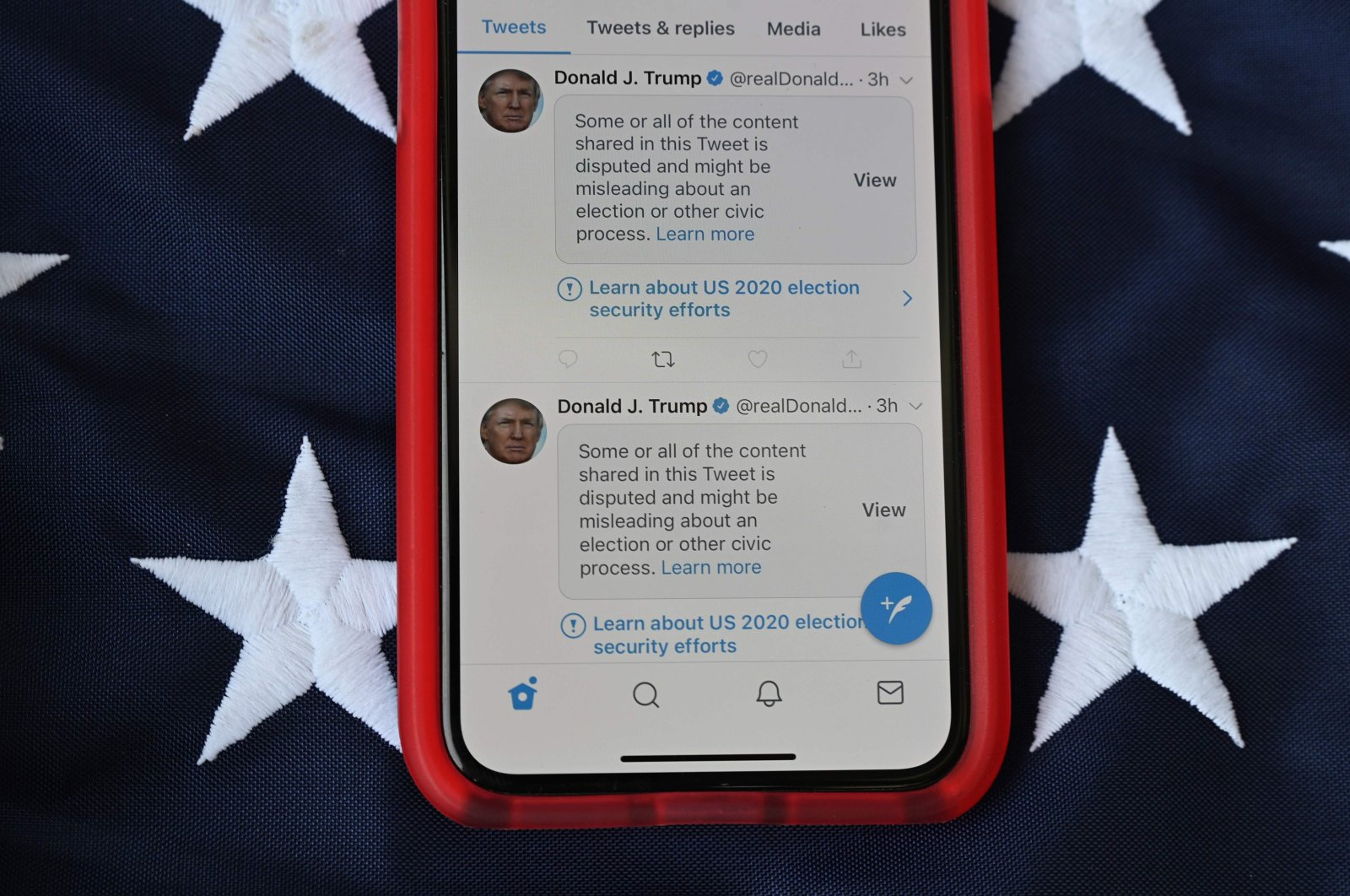 This illustration photo shows a mobile phone placed on a U.S. flag with tweets from then U.S. President Donald Trump masked with warnings imposed by Twitter stating that they may be incorrect, Nov. 5, 2020. (AFP Photo)