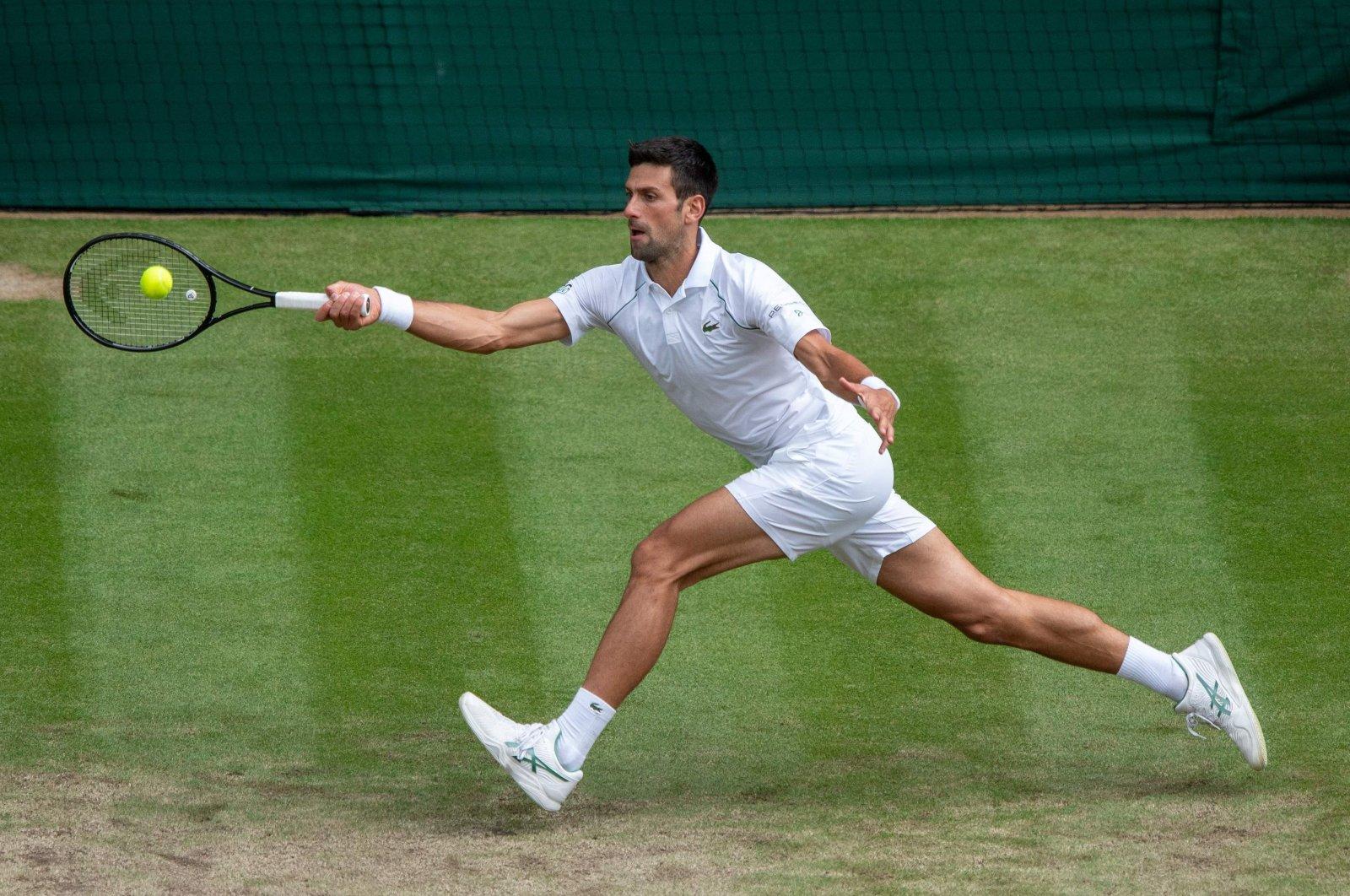 Serbia's Novak Djokovic returns a shot against Hungary's Marton Fucsovics during the Wimbledon men's quarterfinals at The All England Tennis Club in Wimbledon, southwest London, July 7, 2021. (AFP Photo)