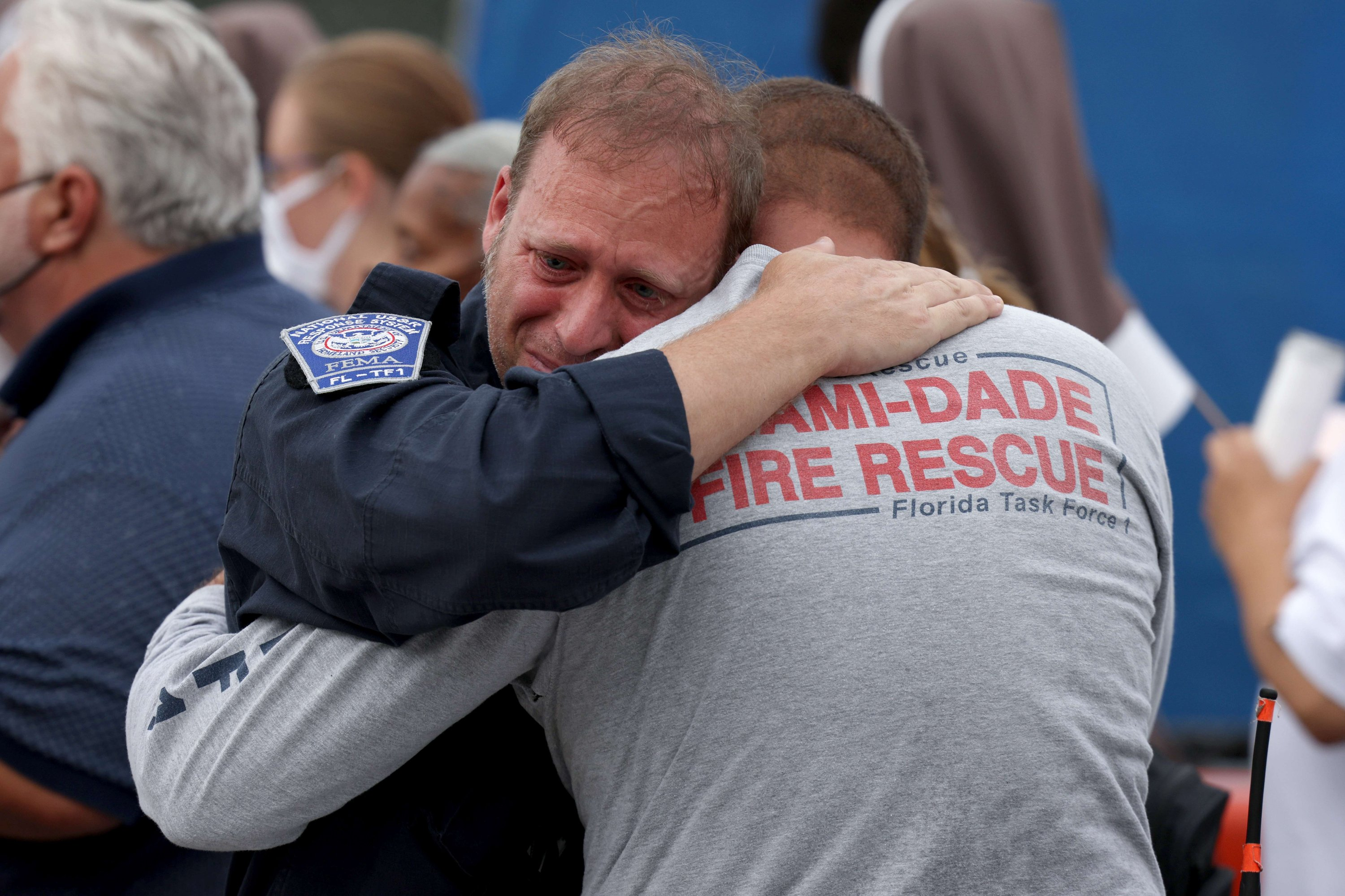 Members of the search and rescue team embrace after a moment of silence in front of the rubble of the collapsed Champlain Towers South building in Surfside, U.S. July 7, 2021. (AFP Photo)