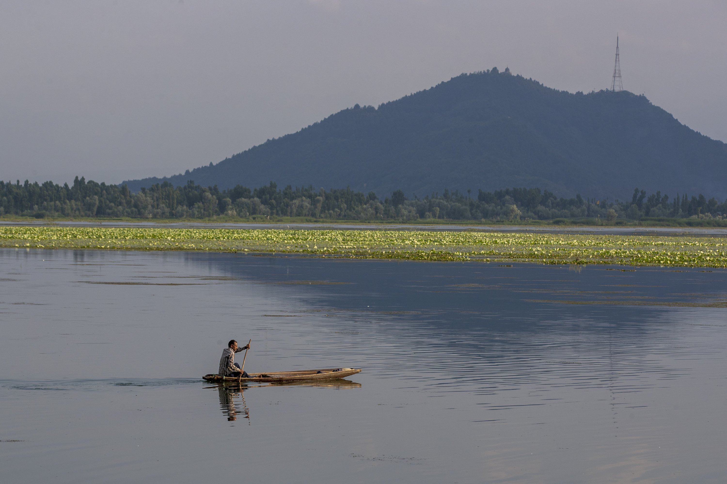 A Kashmiri man rows his Shikara, a traditional boat, as he heads home after a day's work on the Dal Lake on the outskirts of Srinagar, Indian-controlled Kashmir, July 3, 2021. (AP Photo)