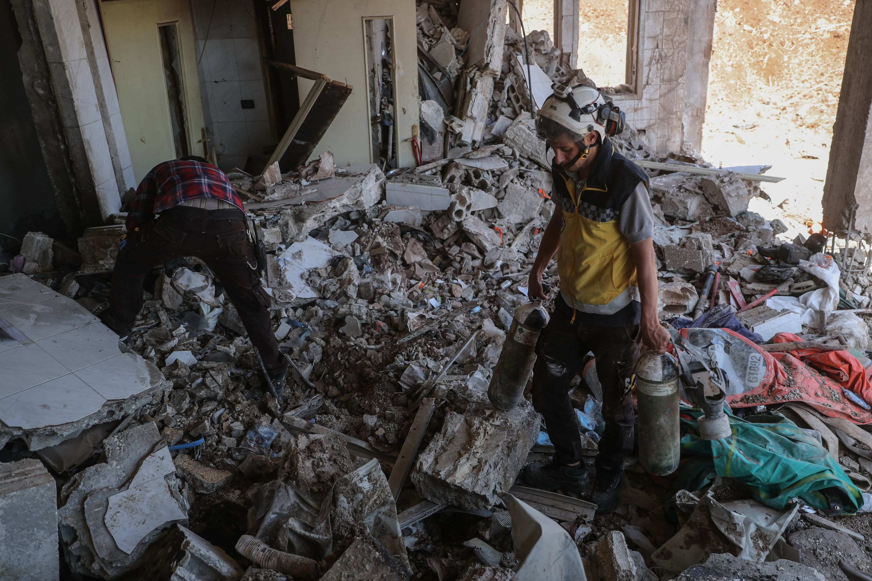 Members of the Syria Civil Defence, known as White Helmets, inspect the rubble of a damaged Civil Defence center after it was targeted by warplanes, Idlib, Syria, July 3, 2021. (Getty Images)