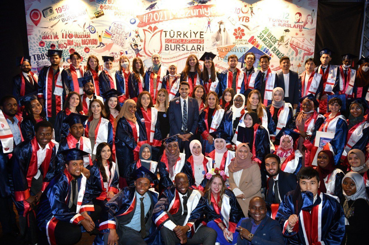 Graduates pose with YTB President Abdullah Eren (C) at the graduation ceremony in the capital Ankara, Turkey, on July 7, 2021. (COURTESY OF YTB)