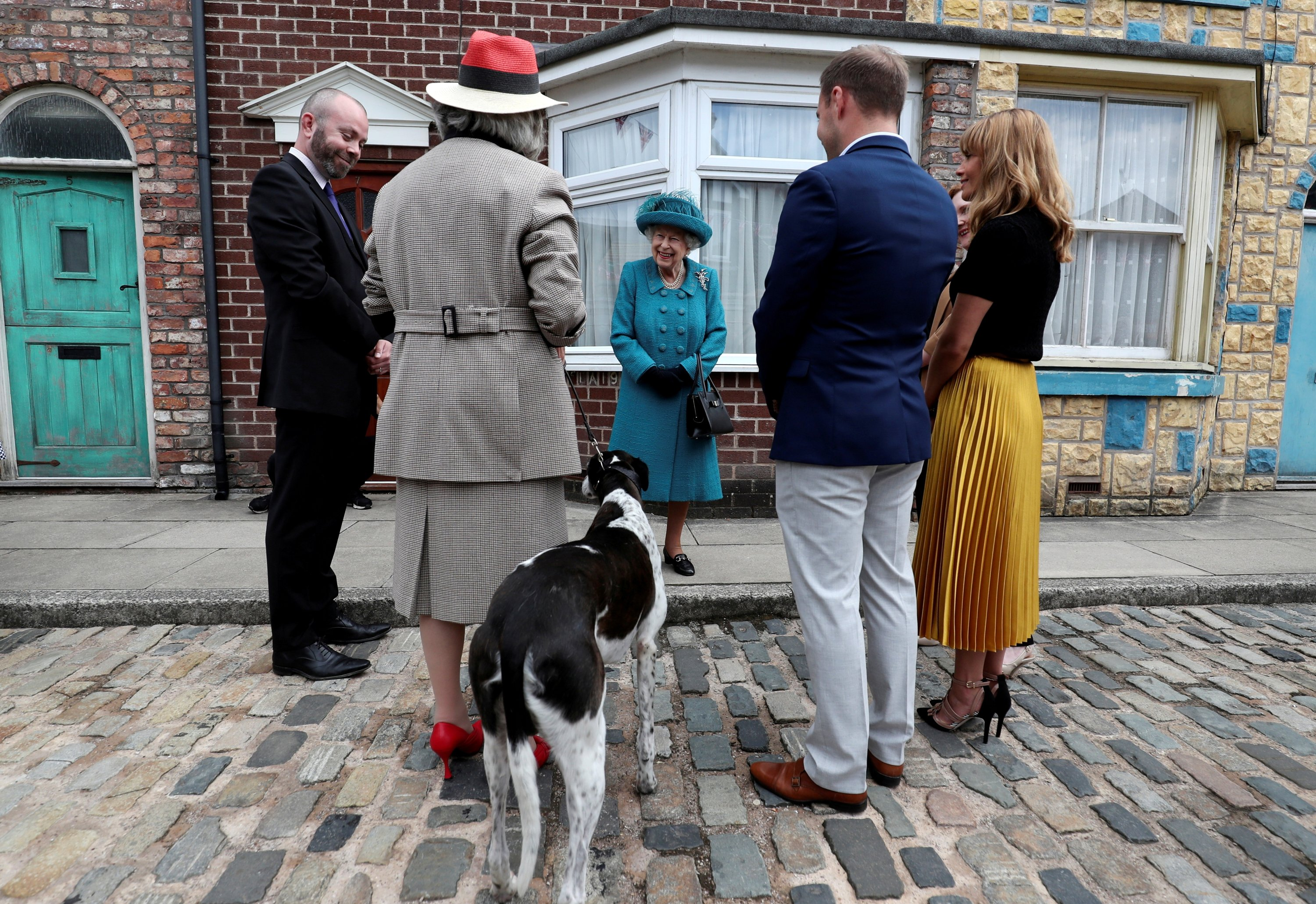 Britain's Queen Elizabeth (C) meets actors and members of the production team during a visit to the set of the long-running television series 'Coronation Street,' in Manchester, Britain, July 8, 2021. (Pool Photo via Reuters)