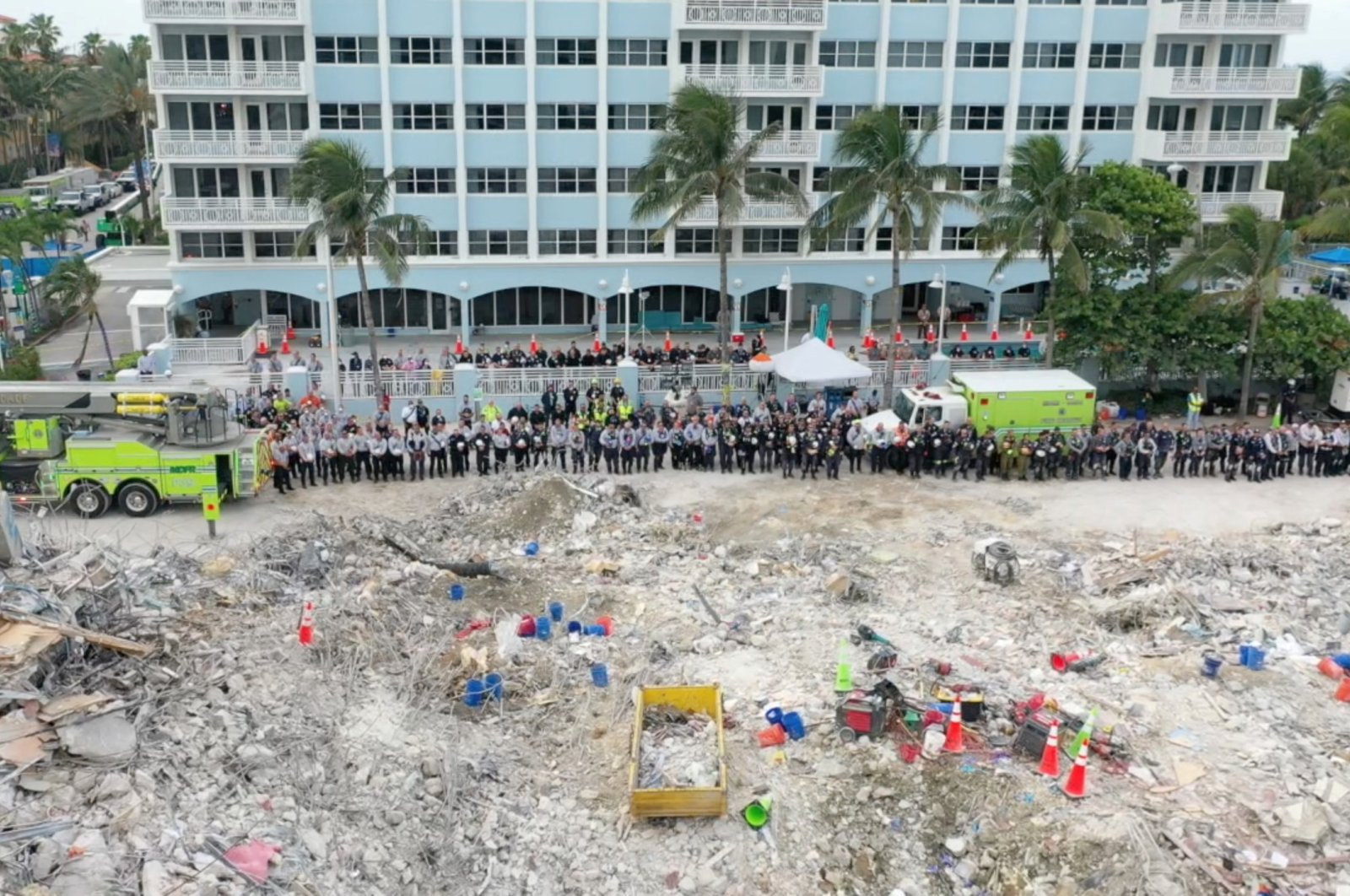 Members of the search and rescue team stand during a moment of silence in front of the rubble of the collapsed Champlain Towers South building in Surfside, Florida, U.S. July 7, 2021, (Reuters Photo)