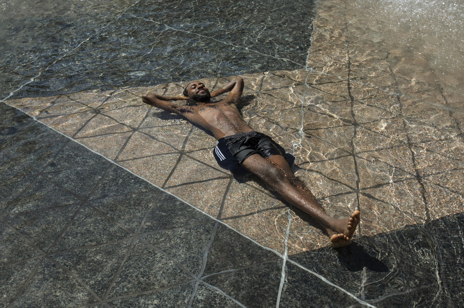 A man relaxes in the cool in the city hall pool, as temperatures hit 37 degrees Celsius in Edmonton, Alberta, Canada, June 30, 2021. (The Canadian Press via AP)