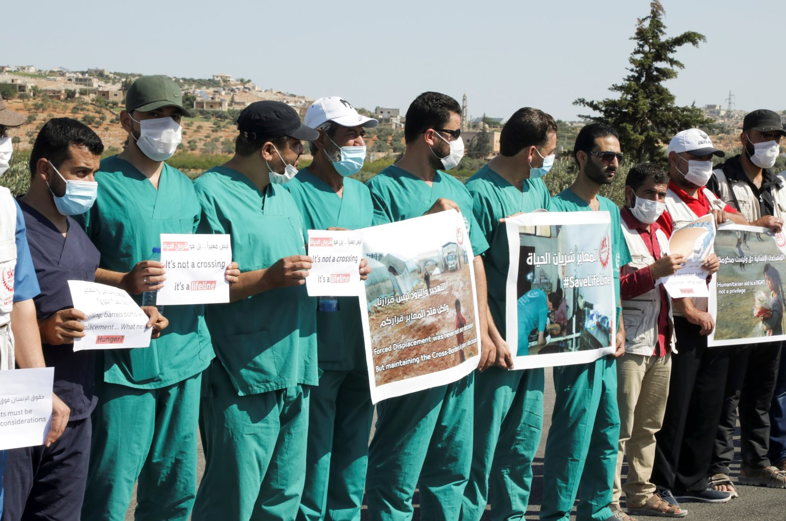 Health care workers hold signs near the Bab al-Hawa crossing during a sit-in against its closure, at the Syrian-Turkish border, in Idlib governorate, Syria, July 2, 2021. (Reuters Photo)