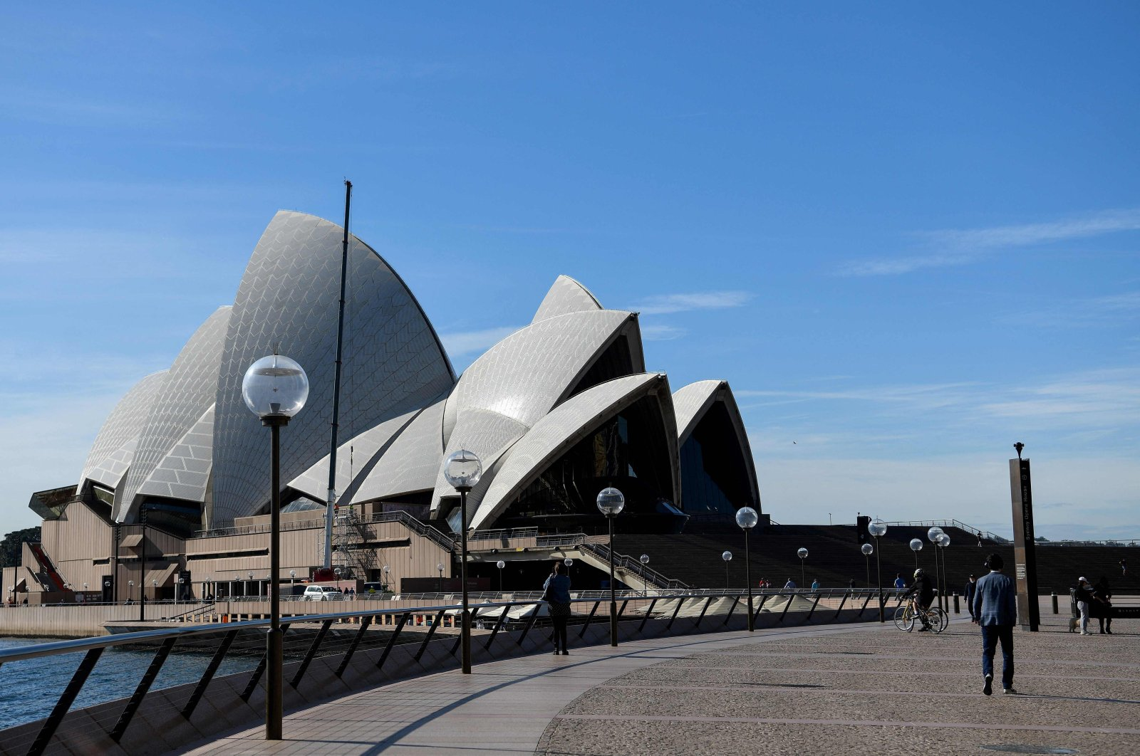 People walk through an unusually quiet Sydney Opera House forecourt as the city remains in lockdown for a second week to contain an outbreak of the highly contagious delta COVID-19 variant, Sydney, Australia, July 6, 2021. (AFP Photo)