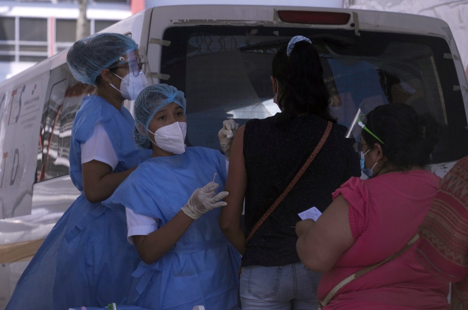 A health care workers inoculate women with the AstraZeneca COVID-19 vaccine, outside the Rommel Fernandez soccer stadium where the parking lot has been converted into a vaccination site in Panama City, Florida, U.S., June 28, 2021. (AP Photo)
