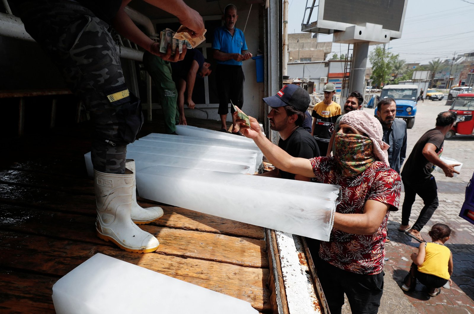Iraqis buy ice blocks at a factory in Sadr City, east of the capital Baghdad, amid power outages and soaring temperatures, Iraq, July 2, 2021. (AFP Photo)