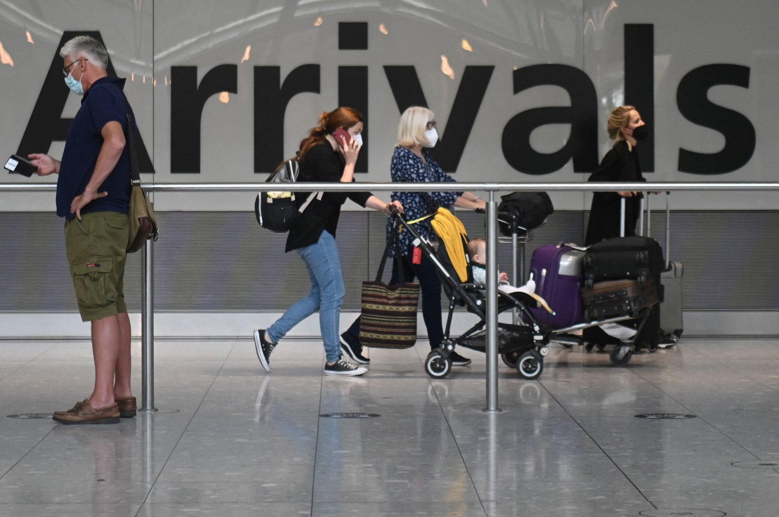 Passengers push their luggage on arrival in Terminal 5 at Heathrow airport, London, June 3, 2021. (AFP Photo)