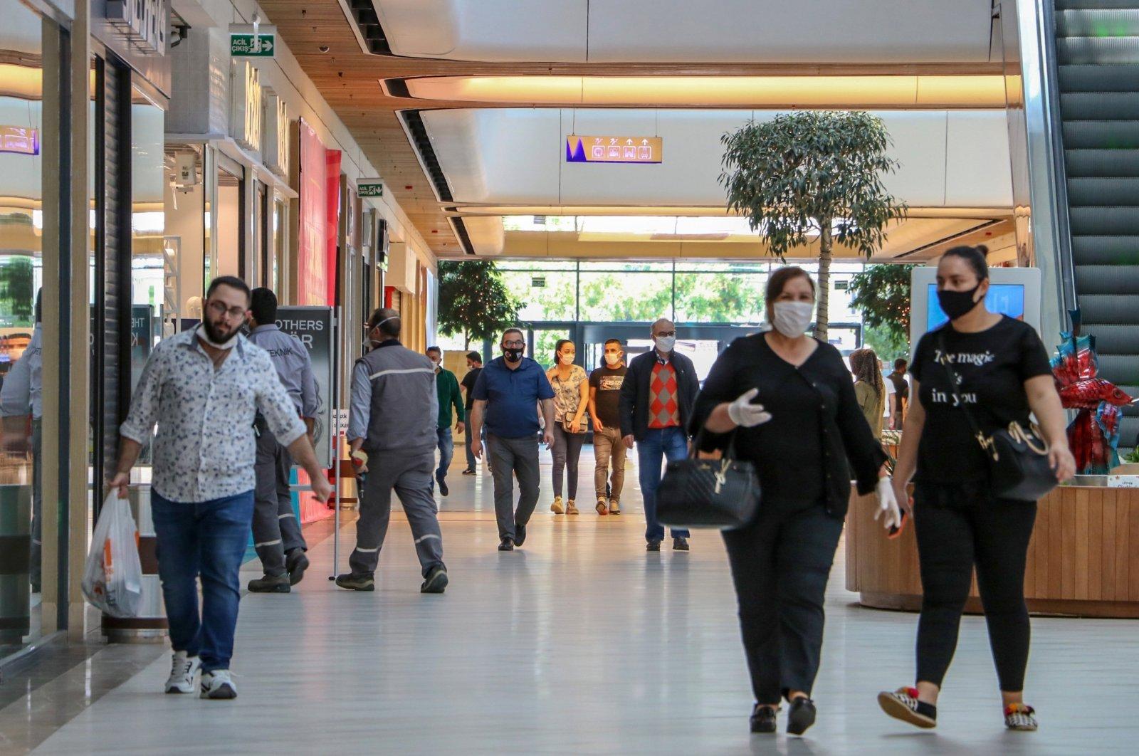 People wearing protective masks walk inside a shopping mall in Antalya, southern Turkey, May 13, 2020. (DHA Photo)