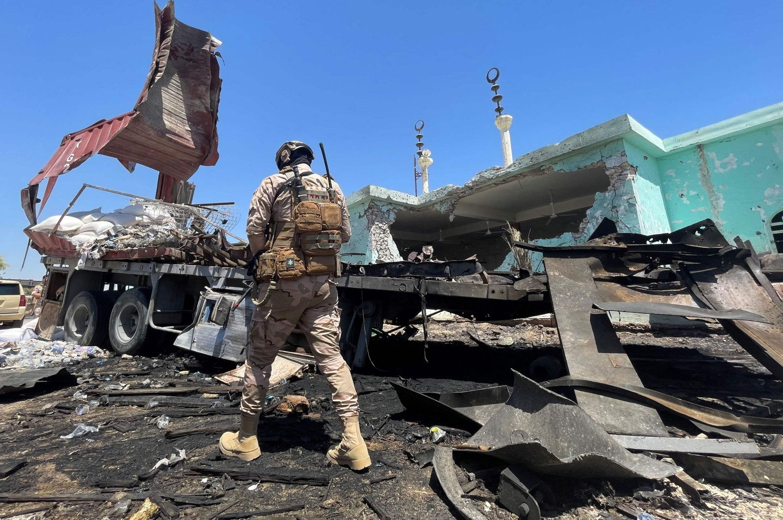 A member of the Iraqi security forces walks past a destroyed vehicle that was carrying rockets amdist sacks of flour, in the district of al-Baghdadi in al-Anbar province on July 8, 2021. (AFP Photo)