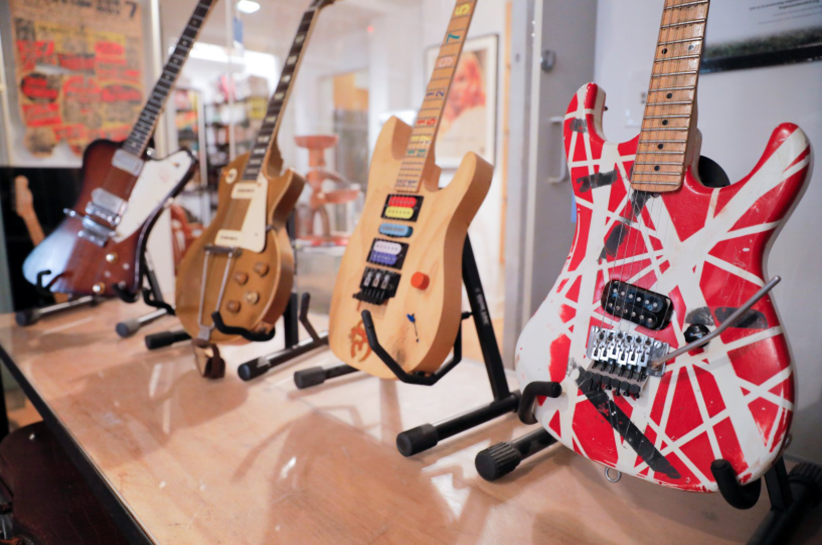 """(L-R) A Gibson Firebird guitar that belonged to Allen Collins of Lynyrd Skynyrd, a single owner 1952 Gibson Les Paul gold top, Jason Becker's """"Numbers"""" guitar and Eddie Van Halen's Kramer Stryper guitar are seen on stands ahead of the """"Century of Music"""" auction held at Guernsey's auction house in New York City, New York, U.S., July 6, 2021. (REUTERS Photo)"""