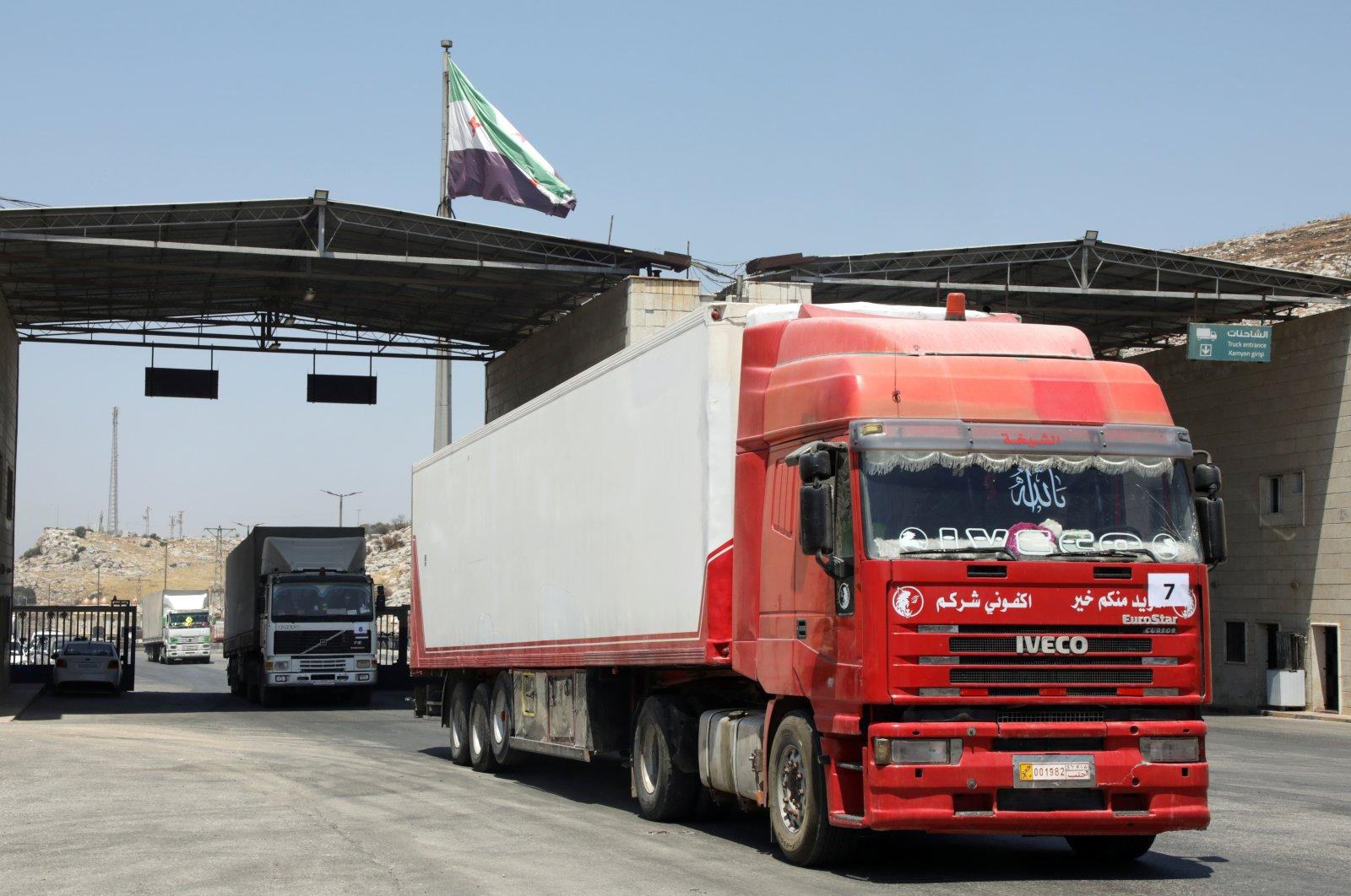 Trucks drive at Bab al-Hawa crossing at the Syrian-Turkish border, in Idlib governorate, Syria, June 30, 2021. (Reuters Photo)