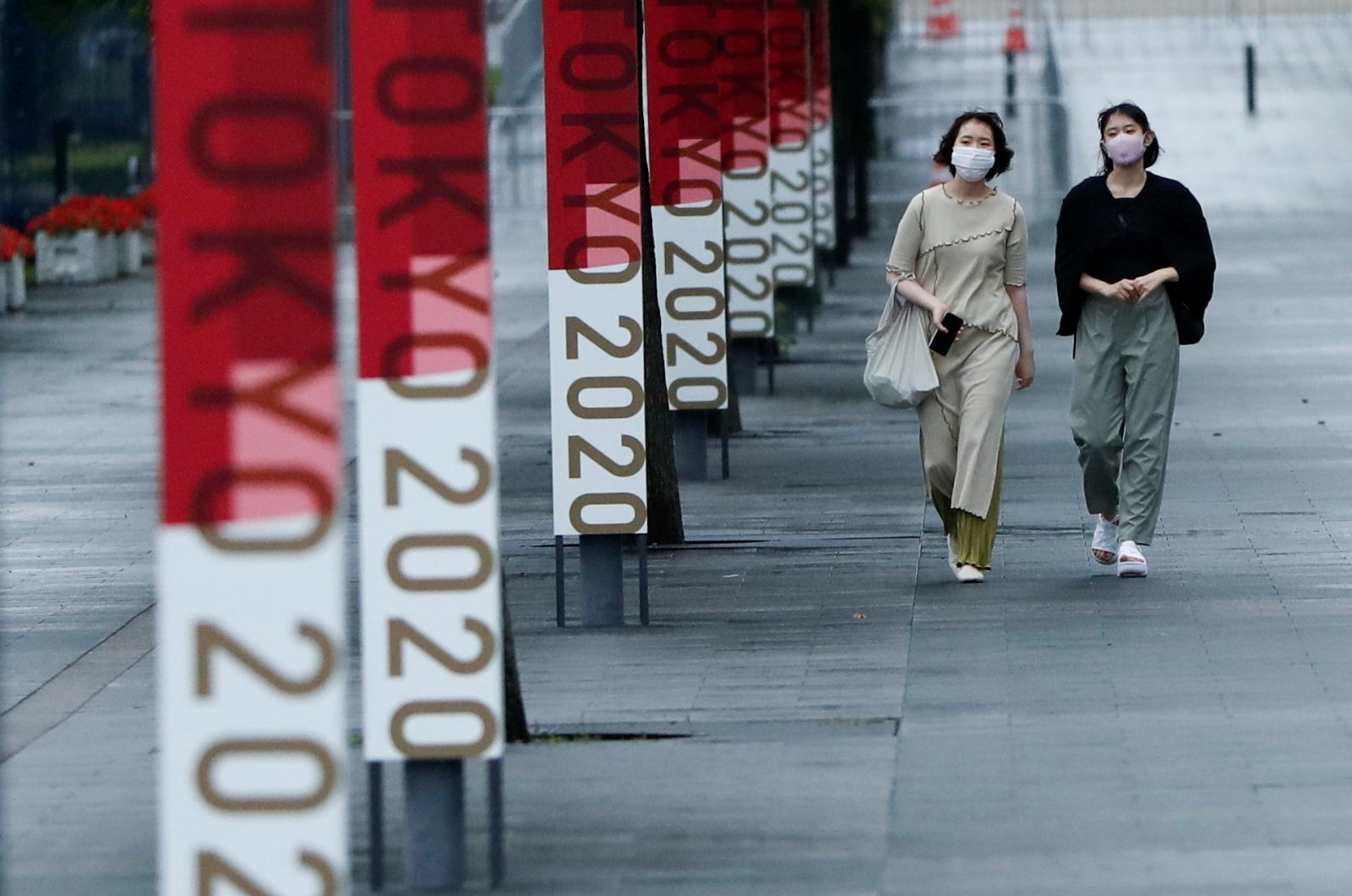 Pedestrians in safety masks against COVID-19 walk past Tokyo 2020 Olympic Games advertising in the Centre Promenade Park, Tokyo, Japan, July 8, 2021. (Reuters Photo)