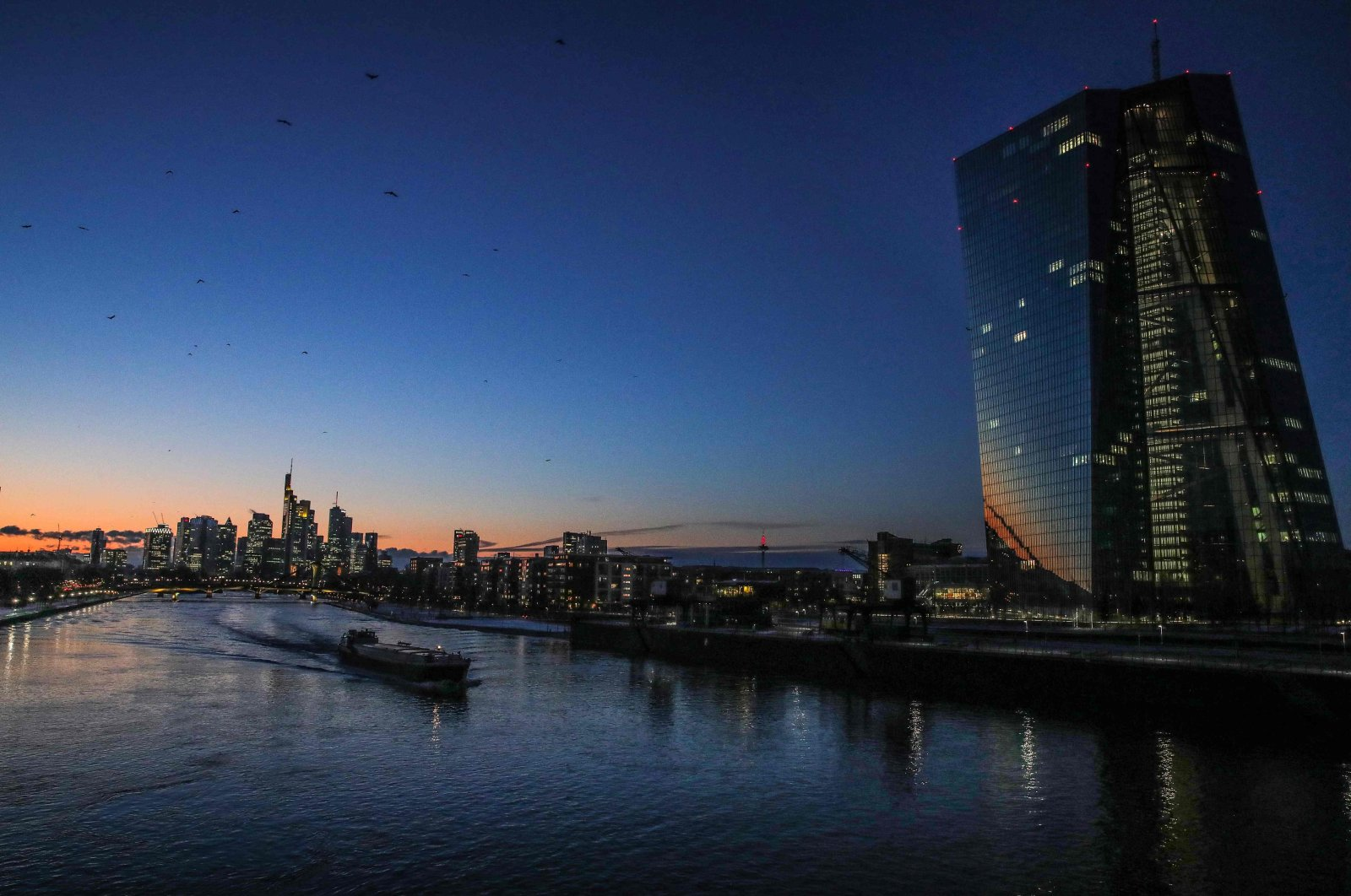 A ship makes its way on the river Main past the headquarters of the European Central Bank (R), with the banking district in Frankfurt am Main in the distance, western Germany, Feb. 10, 2021. (AFP Photo)