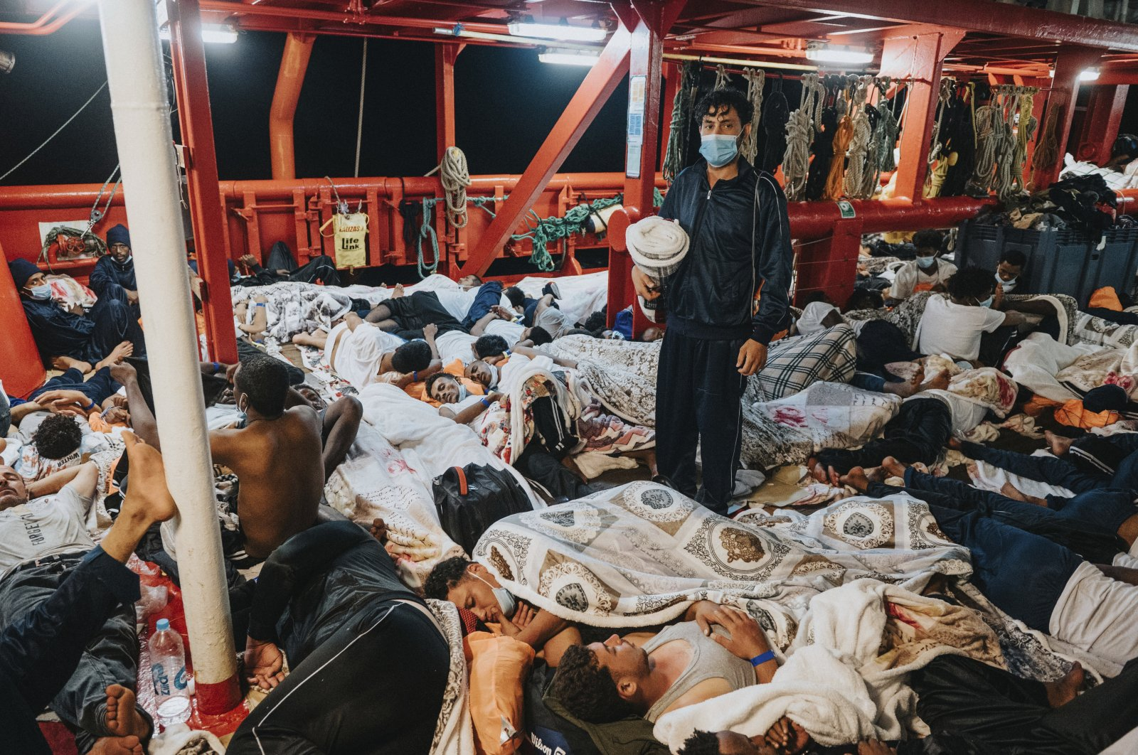 Rescued migrants sleep on the deck of the Ocean Viking rescue ship in the Mediterranean Sea, July 8, 2021. (AP Photo)