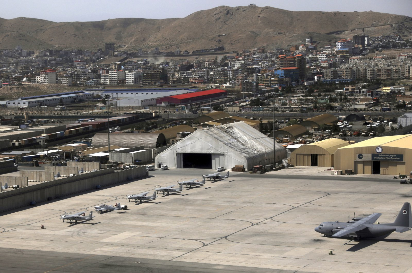 A side of Kabul Military Airport where AC 208 combat caravan aircraft are parked is seen from a commercial airplane, Afghanistan, July 7, 2021. (AP Photo)